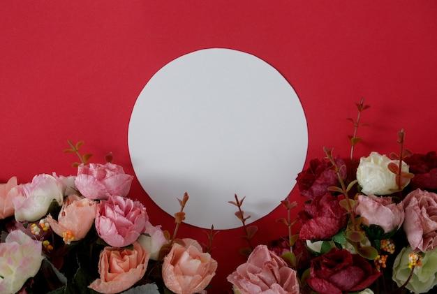 Rundes weißbuch des modells mit platz für text oder bild auf rotem hintergrund und blume. Premium Fotos