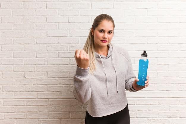 Russische frau der jungen fitness, die einen energiegetränk hält Premium Fotos