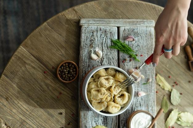 Russische mehlklöße mit sauerrahm, dill und knoblauch auf einem hölzernen behälter Premium Fotos