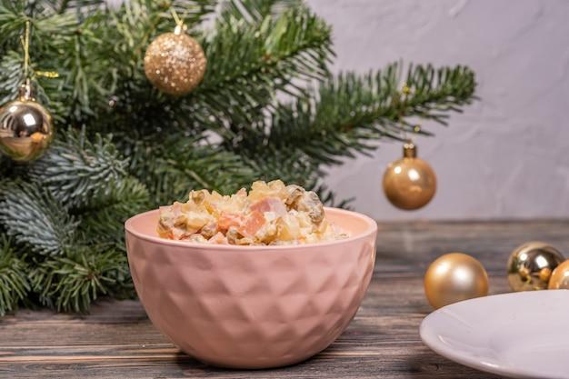 Russischer salat in einer rosa schüssel russischer salat in einer rosa schüssel auf einem geschmückten weihnachtsbaum. olivier. nationales russisches neujahrsgericht. Premium Fotos