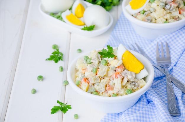 Russischer traditioneller salat olivier mit gemüse und fleisch Premium Fotos