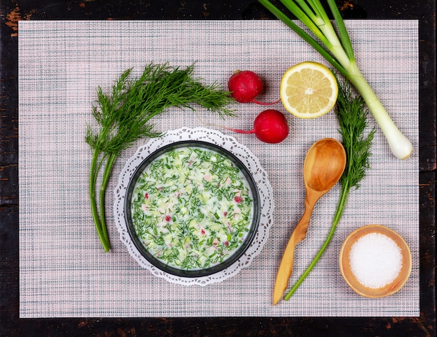 Russisches sommerkältesuppe okroshka vom gemüse, vom kwas und vom kefir mit grüns auf dem tisch Premium Fotos