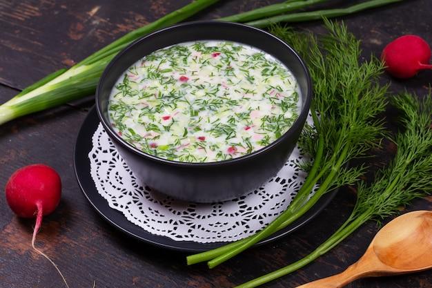 Russisches sommerkältesuppe okroshka von den grüns, vom gemüse, vom kwas und vom kefir auf einem schwarzen holztisch Premium Fotos