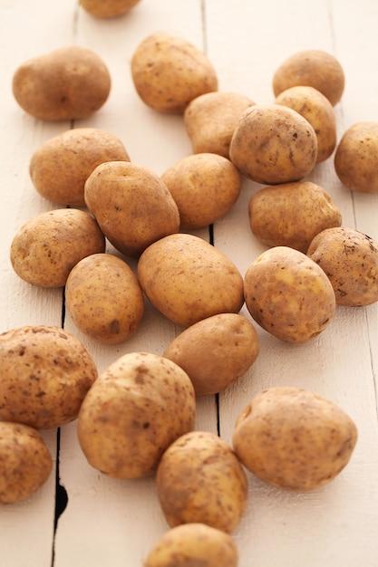 Rustikale ungeschälte kartoffeln auf einer tabelle Kostenlose Fotos