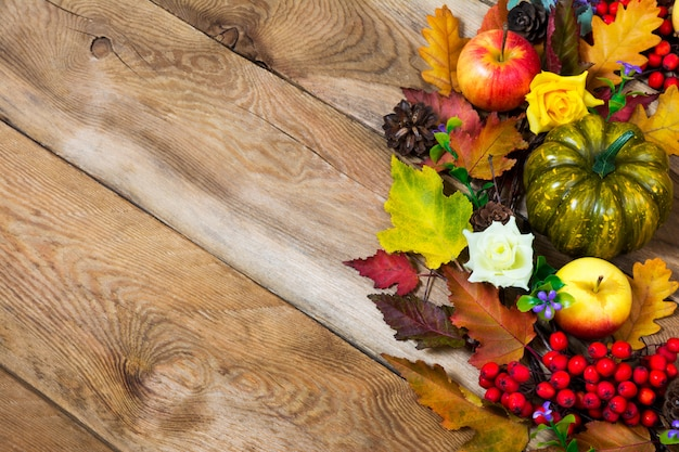 Rustikaler hintergrund des falles mit bunten fallblättern, grünem kürbis, apfel, lila blumen und roten beeren, kopienraum Premium Fotos
