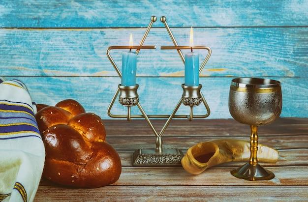 Sabbat-jüdisches feiertagschallahbrot und -candelas auf holztisch Premium Fotos