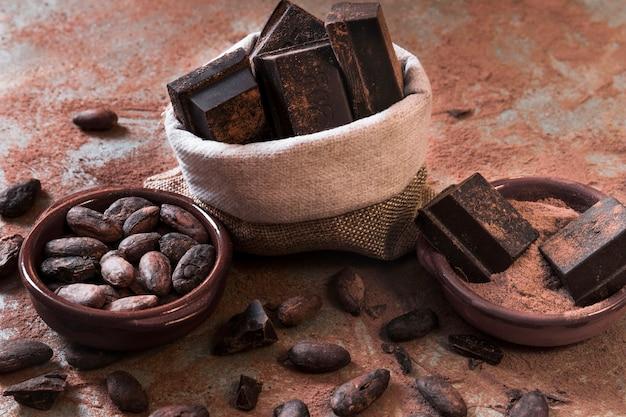 Sack schokoriegelstücke und kakaopulver und bohnen auf unordentlicher tischplatte Kostenlose Fotos