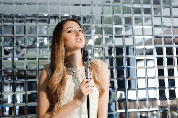Sänger vor einem mikrofon in einem restaurant Premium Fotos