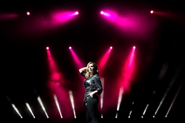 Sängerin der jungen frau mit bunten lichtern auf konzert Premium Fotos
