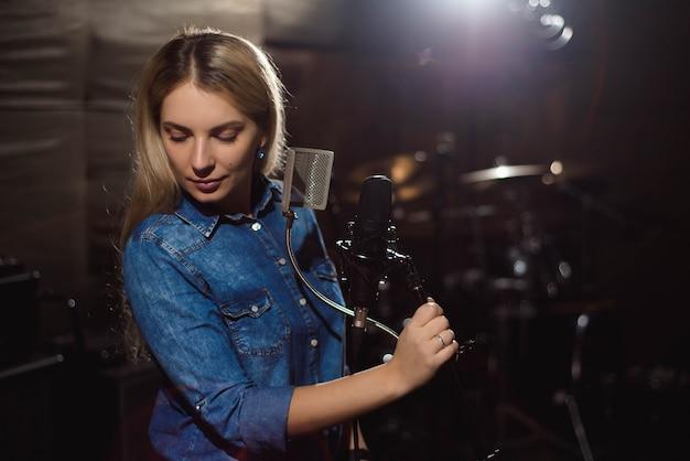 Sängerin, die ein lied singt. frau, die in einem tonstudio durchführt Premium Fotos