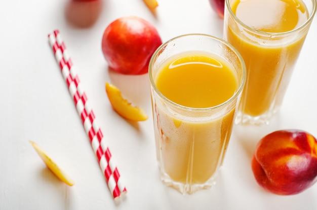 Saft von den pfirsichen und von den nektarinen mit masse mit frischen früchten auf einem weißen hintergrund. Premium Fotos