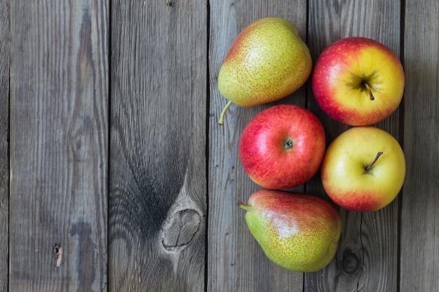 Saftige äpfel und birnen liegen auf einem natürlichen holztisch. speicherplatz kopieren Premium Fotos