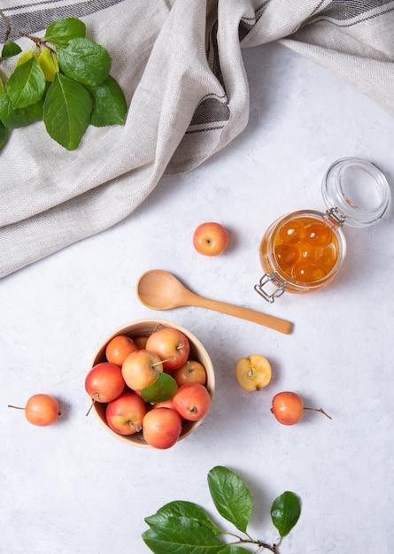Saftige mini-äpfel in einer holzschale und einem glas marmelade Premium Fotos