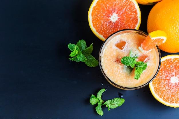 Saftige orangen mit einem orangensaft Kostenlose Fotos
