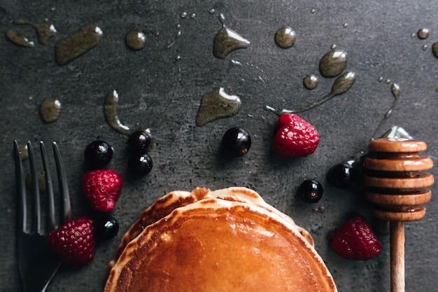Saftige pfannkuchen mit beeren, honig, löffel auf einem schwarz-grauen betontisch. hochwertiges foto Premium Fotos