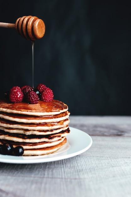 Saftige pfannkuchen mit beeren und honig auf einem weißen teller, löffel, holztisch. hochwertiges foto Premium Fotos