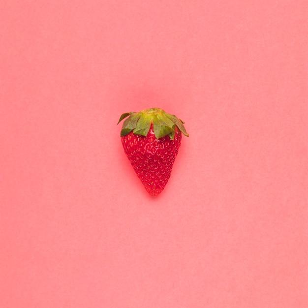Saftige rote erdbeere auf rosa hintergrund Kostenlose Fotos