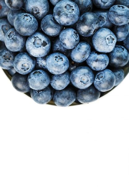 Saftige und reife blaubeeren in einer weißen platte auf einem weißen hintergrund Premium Fotos