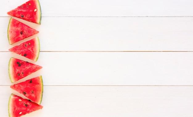 Saftige wassermelonenscheiben entwerfen auf hölzernem weißem plankenhintergrund Kostenlose Fotos