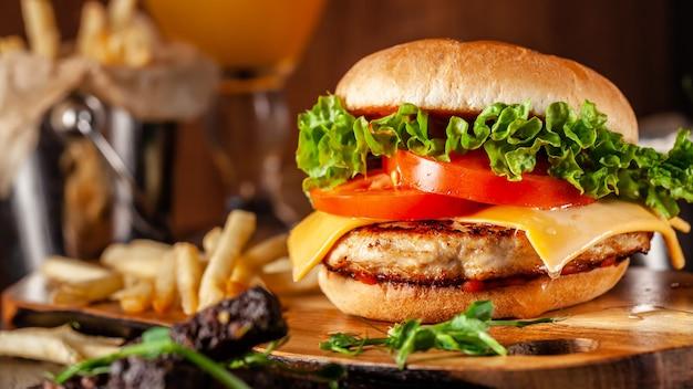 Saftiger burger mit fleischpastetchen, tomaten, cheddar-käse, salat und hausgemachtem brötchen. Premium Fotos