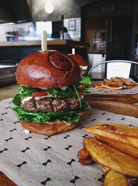 Saftiger rindfleischburger mit rucola und kartoffelecken Kostenlose Fotos