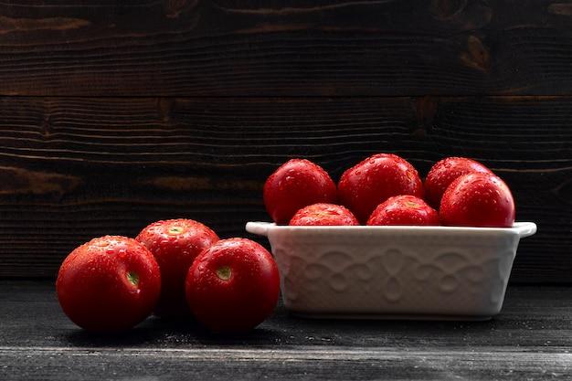 Saftiges rotes tomatenstillleben auf dunklem hintergrund Premium Fotos