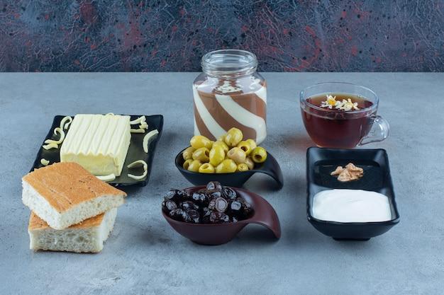 Sahne, honig, schokolade, brot, käse, schwarze und grüne oliven und eine tasse tee auf marmortisch. Kostenlose Fotos