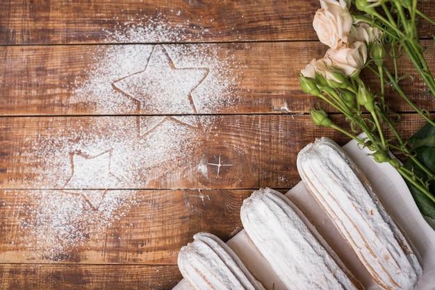 Sahnige gebackene eclairs mit rosa rosen mit den sternen gezeichnet auf zuckerpulver über dem hölzernen schreibtisch Kostenlose Fotos
