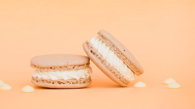 Sahnige köstliche makronen auf beige hintergrund Kostenlose Fotos