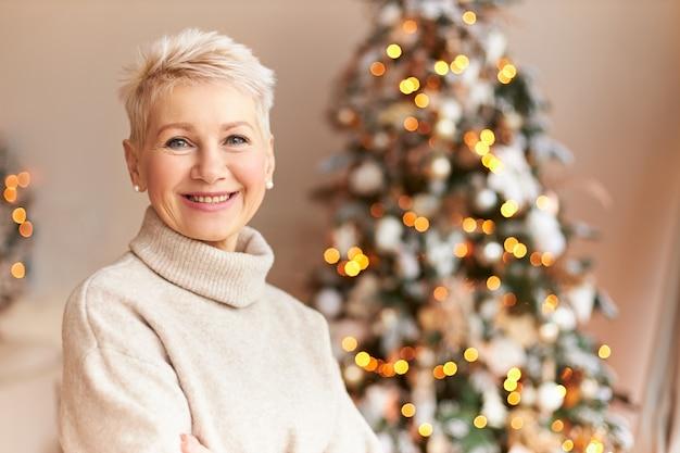 Saison-, winter-, ferien- und feierkonzept. bild der fröhlichen dame mittleren alters mit dem kurzhaarigen und breiten strahlenden lächeln, das vorbereitungen für weihnachten genießt und an geschmückter kiefer zu hause aufwirft Kostenlose Fotos