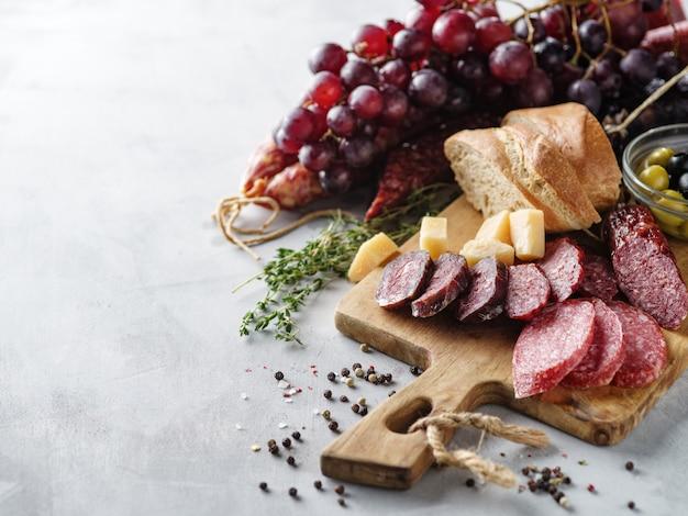 Salami im rustikalen stil geschnitten. salami-wurst. verschiedene würste mit käse, trauben und oliven Premium Fotos