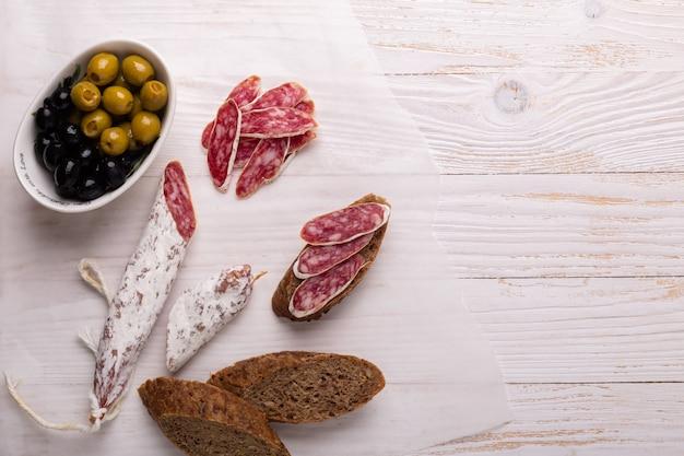 Salami und brot auf weißem hölzernem hintergrund. ansicht von oben. Premium Fotos