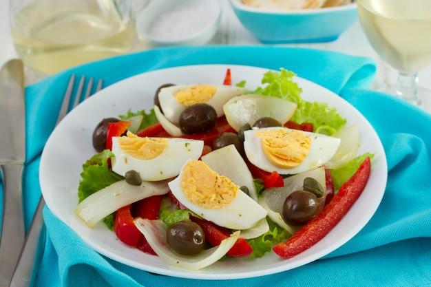 Salat auf weißer platte und glas weißwein Premium Fotos