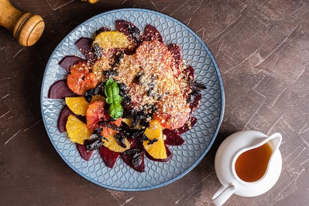 Salat aus roten orangen, zuckerrüben, orangen, gemahlenen mandeln, getrockneten pflaumen, honigsauce. Premium Fotos