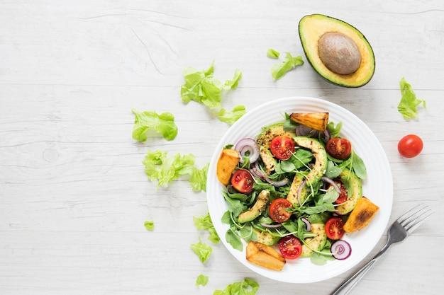 Salat des strengen vegetariers mit avocado auf weißem holztisch Premium Fotos