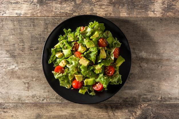 Salat mit avocado, kopfsalat, tomate, leinsamen auf draufsicht des holztischs Premium Fotos