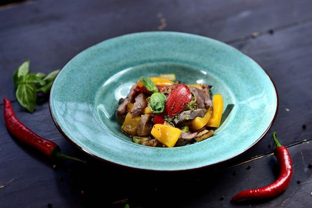 Salat mit fleisch, paprika, tomaten und basilikum, in einem türkisfarbenen teller auf einem holzofen Premium Fotos