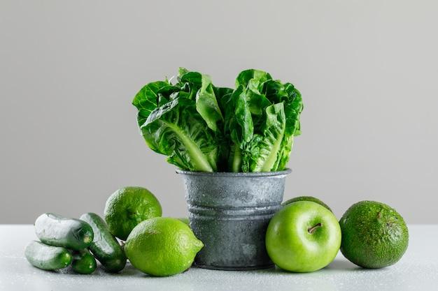 Salat mit gurke, limette, apfel, avocado in einem mini-eimer auf weißem und grauem tisch Kostenlose Fotos