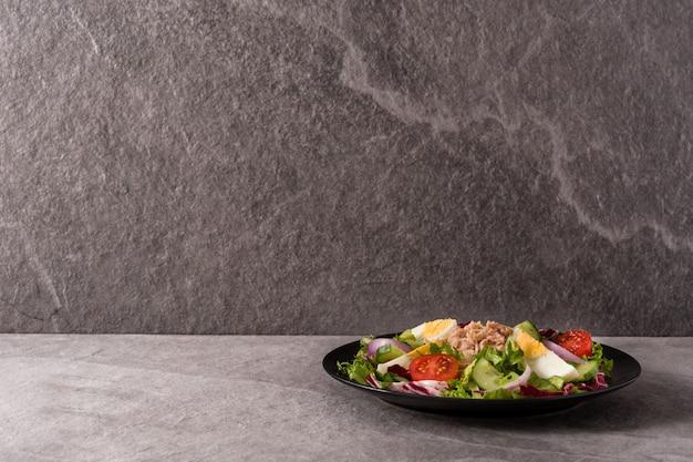 Salat mit thunfisch, ei und gemüse auf schwarzblech und grauer oberfläche Premium Fotos