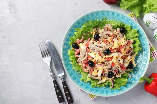 Salat mit zunge, paprika, eiern, salat, käse und schwarzen oliven auf blauem teller auf grauer oberfläche. draufsicht. platz für text Premium Fotos
