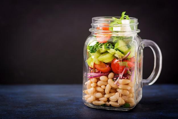 Salat von weißen bohnen, von tomate, von sellerie, von gurke, von arugula, von roter zwiebel und von feta in einem ja Premium Fotos