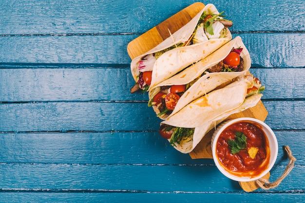 Salsa-sauce; mexikanische tacos mit fleisch und gemüse auf schneidebrett über blauem holzbrett Premium Fotos