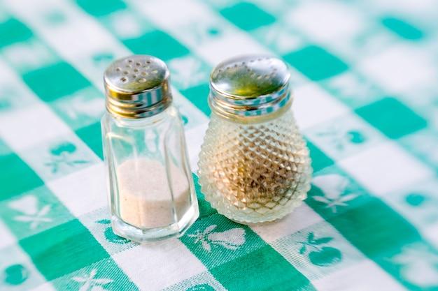 Salz- und pfefferstreuer auf einer grünen karierten tischdecke Premium Fotos