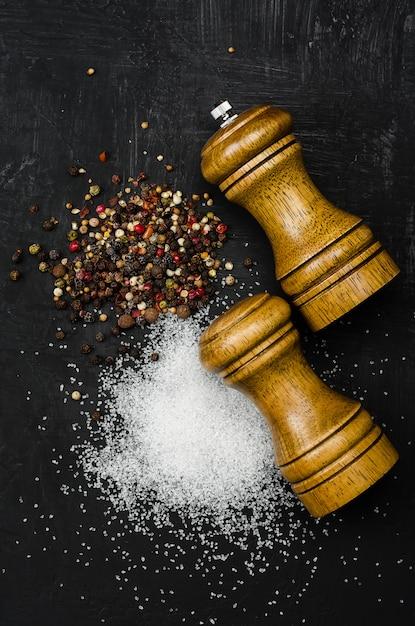 Salz- und pfefferstreuer aus holz. gewürzsalz und pfeffer auf schwarzem kreidebrett Premium Fotos