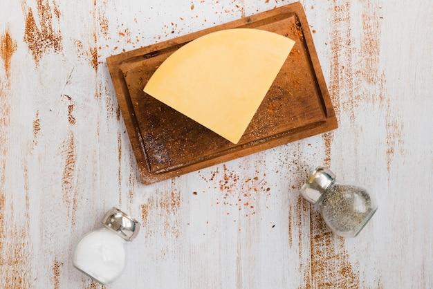 Salz- und pfefferstreuerflaschen mit käse auf hackendem brett Kostenlose Fotos