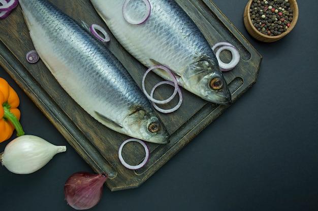 Salzhering mit zwiebeln und kräutern auf einem schneidebrett Premium Fotos