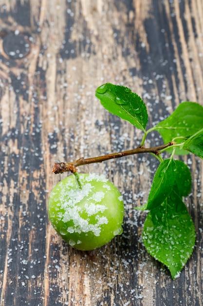 Salzige grüne pflaume mit hohem blickwinkel des zweigs auf eine holzwand Kostenlose Fotos