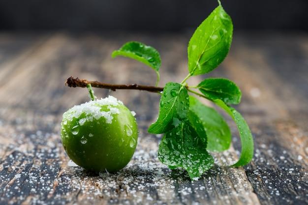 Salzige grüne pflaume mit zweigseitenansicht auf hölzerner und dunkler wand Kostenlose Fotos