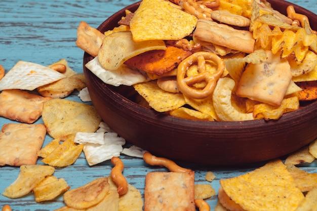 Salzige snacks. brezeln, chips, cracker auf holz. ungesunde produkte Premium Fotos