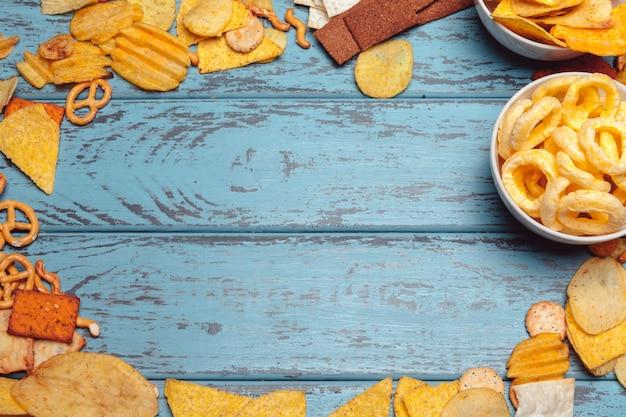 Salziger snackrahmen mit brezeln, chips, cracker auf holzoberfläche Premium Fotos